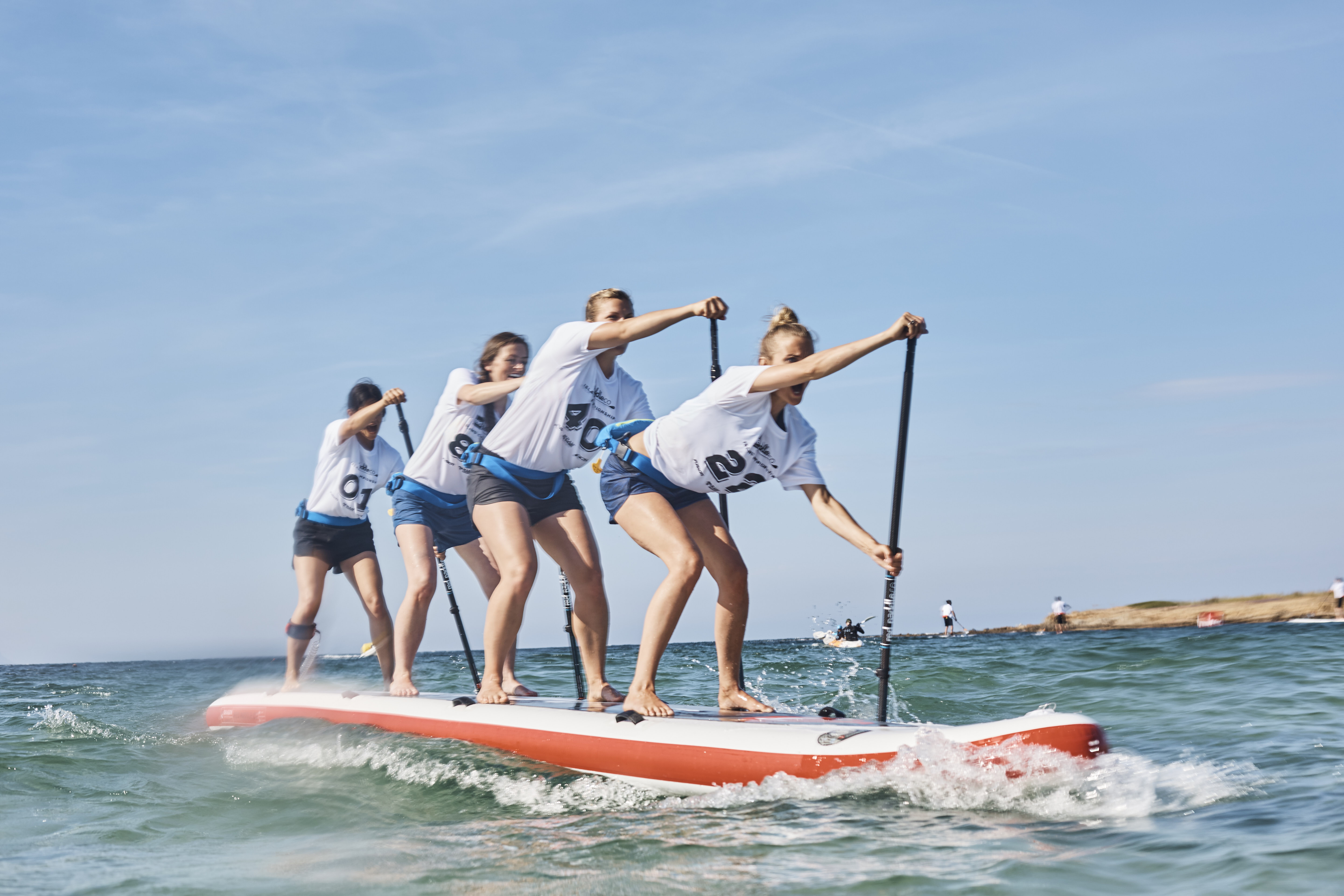 Four women wade into the sea at the Dragon World Championships with the Red Dragon 22ft stand up paddle board.