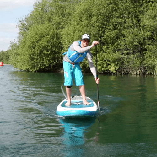 man learning how to stand up paddle board