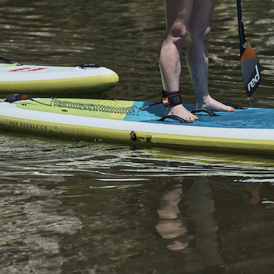 image of red paddle co Voyager board with persons legs