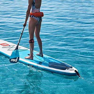 image of woman paddle boarding with straight leash