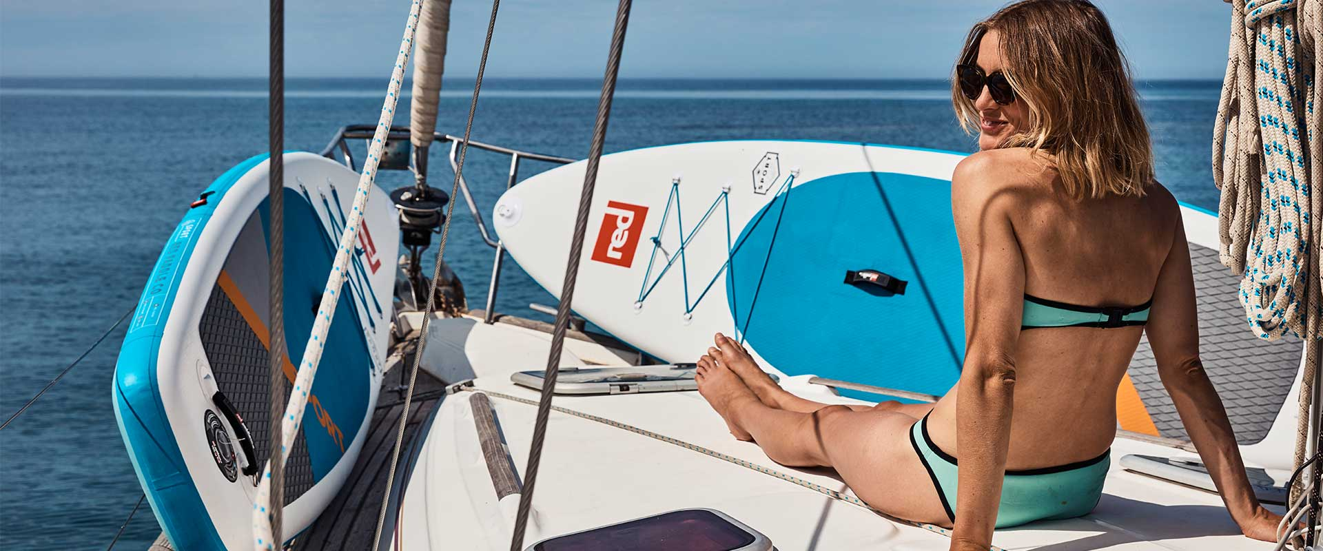 woman on yacht with two sport boards on the front