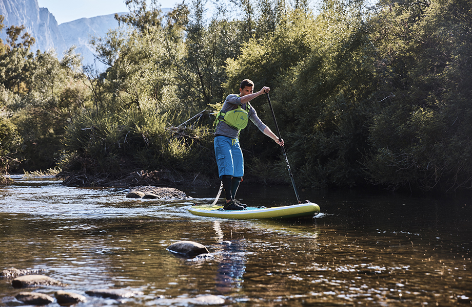 man paddles down river wearing suitable clothing for SUP