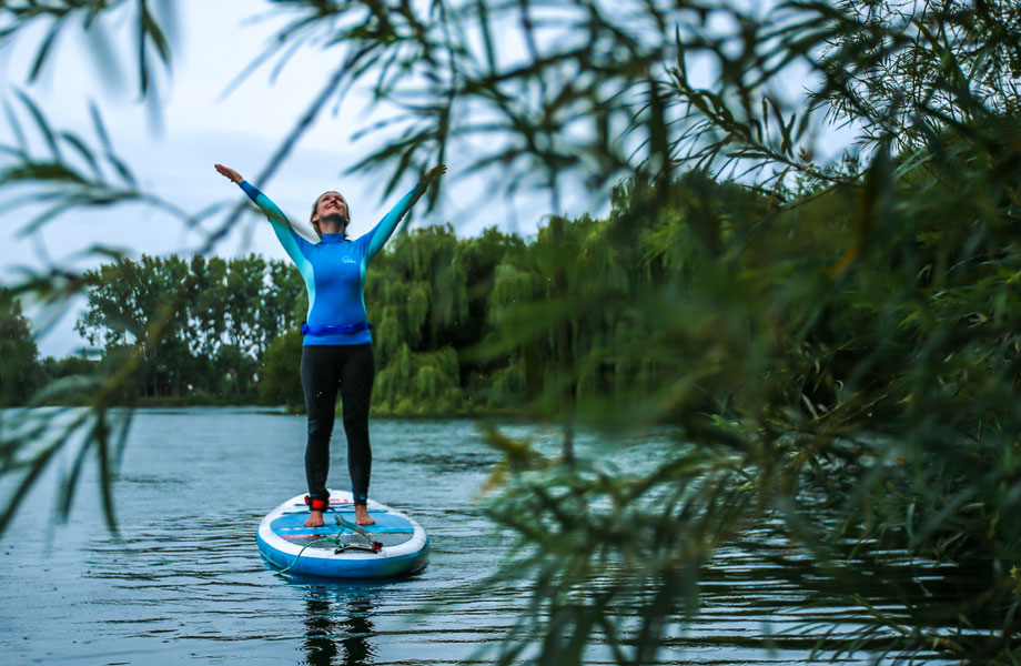 Girl on paddle board doing SUP yoga