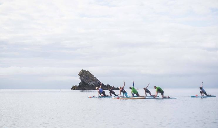 Katy Watson conducting a SUP Yoga session