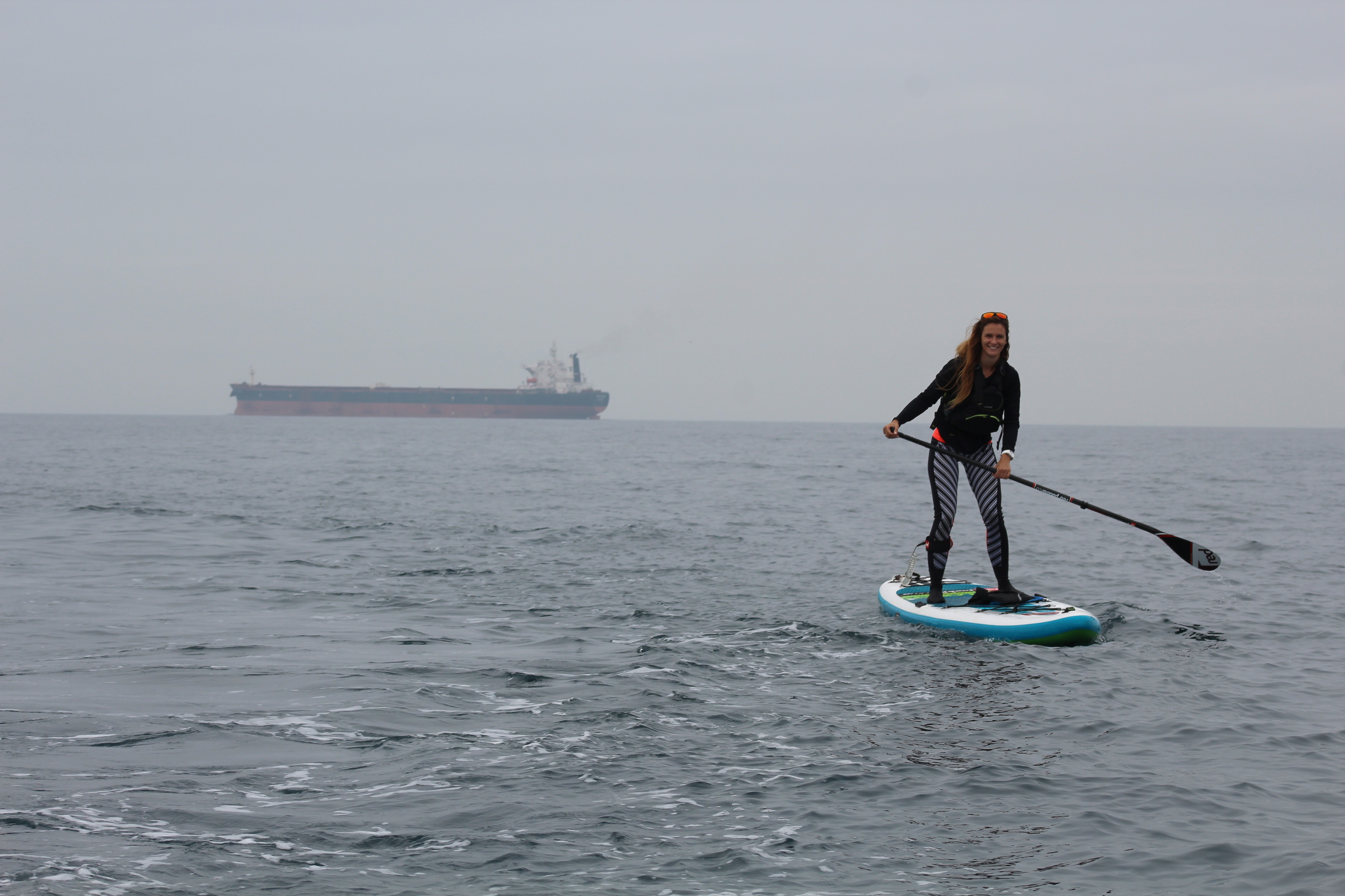 Lizzie paddling on her Red Paddle stand up paddle board, a tanker in the background