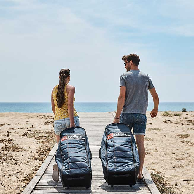 two people rolling Red Paddle Co back packs to the beach