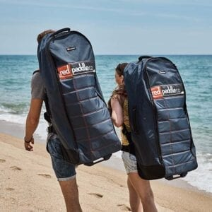 "man and woman walking with red paddle co backpacks containing 10'7"" Wind boards"