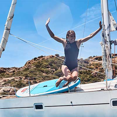 woman jumping off yacht with paddle board on the boat