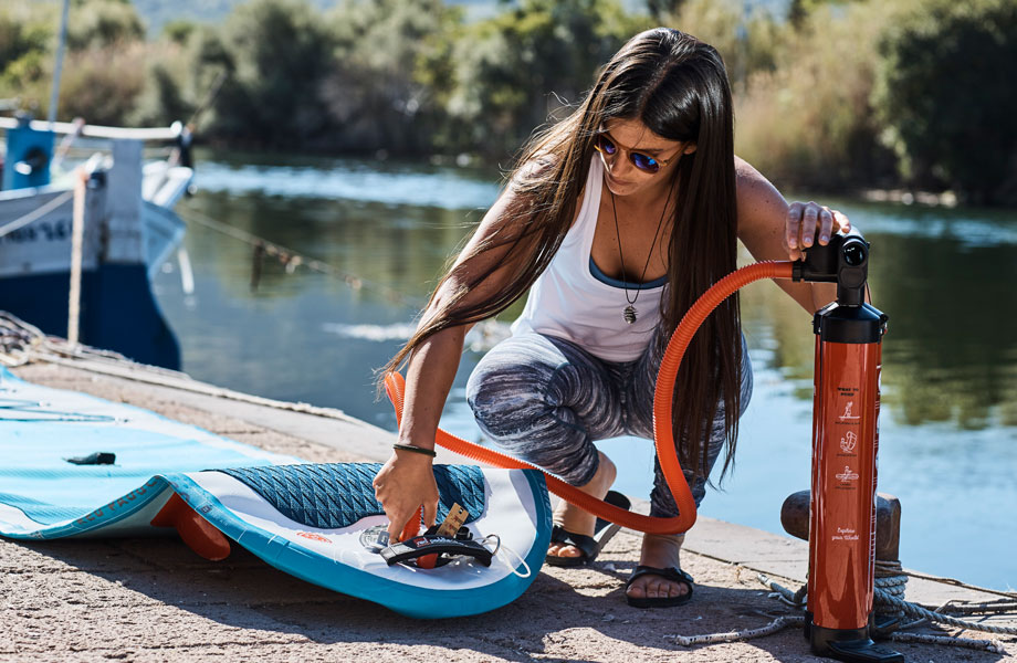 girl inflating her red paddle co board