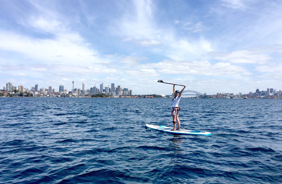 girl celebrated standing on paddle board in front of sydney skyline