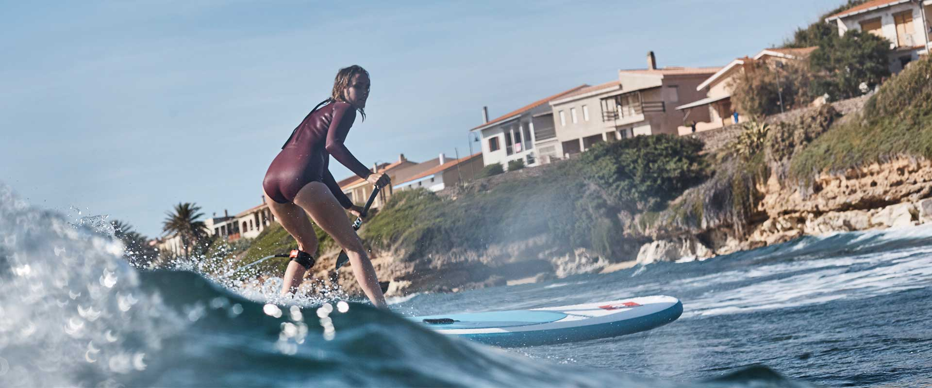 image of girl surfing on red paddle co inflatable whip board