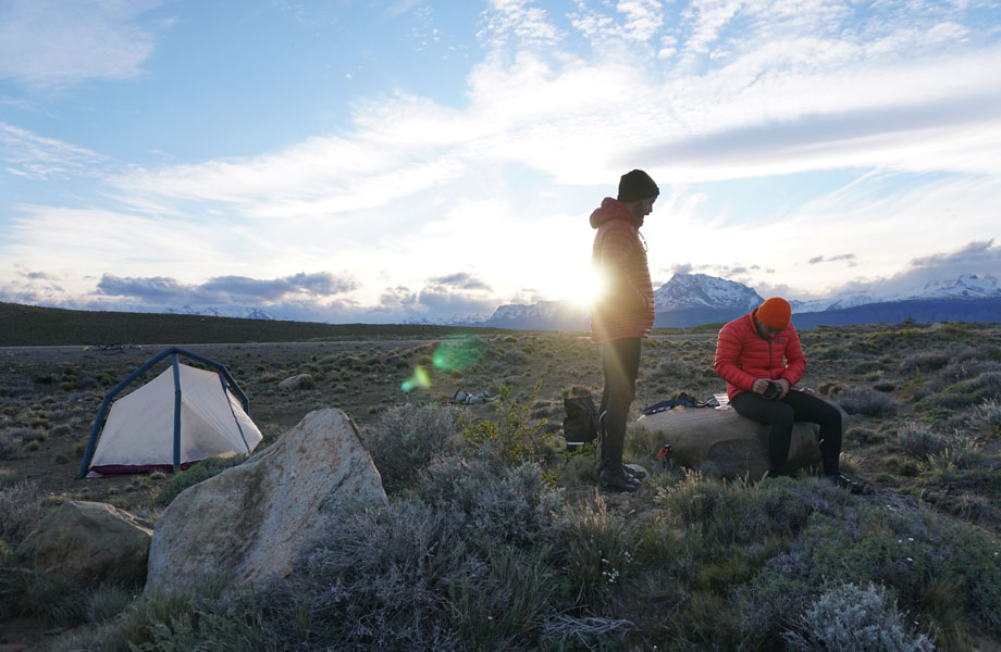 Two men camping prepare breakfast as sun rises over mountains in background