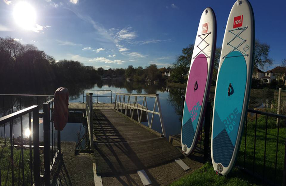 inflatable SUP boards propped up by river