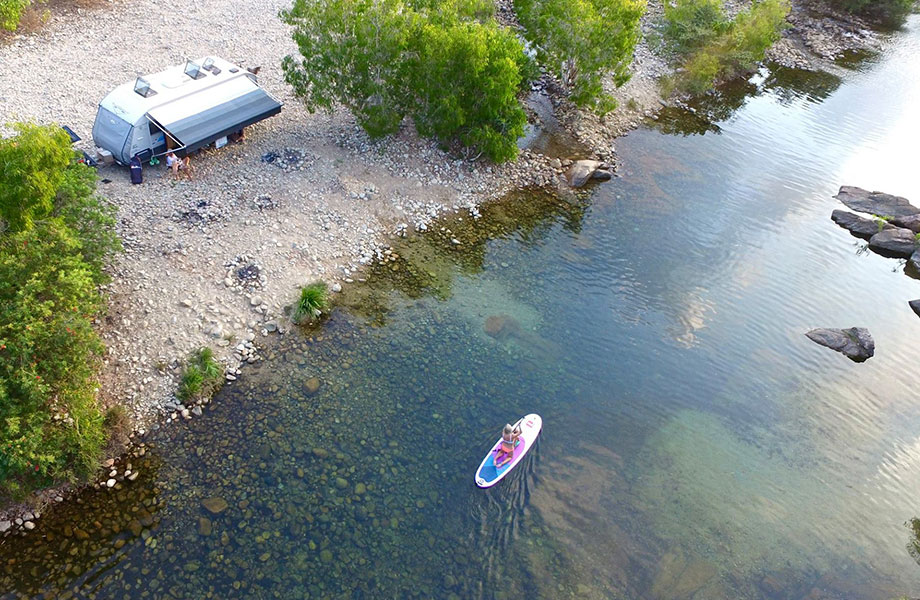 Birdseye view of caravan and paddle boarder