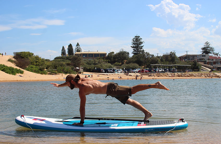 man balances on paddle board for a SUP fit routine