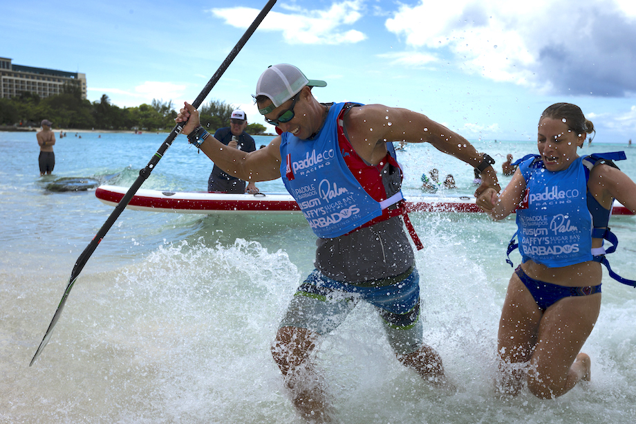 a male and female team members racing to the finish out of the water of a dragon world championships race