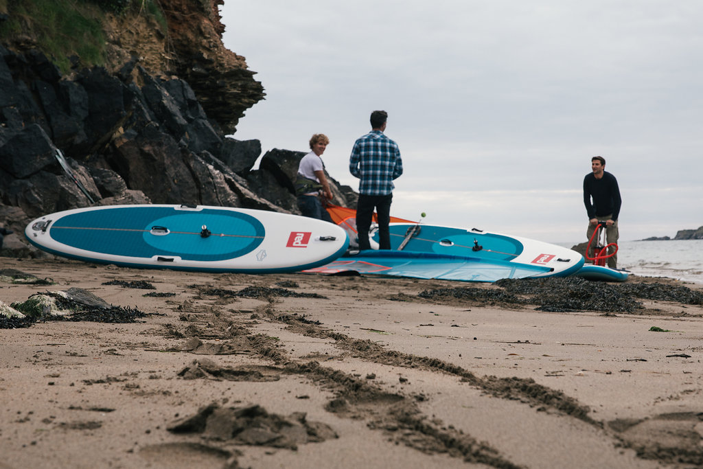 Group of males assembling windsurfing equipment.