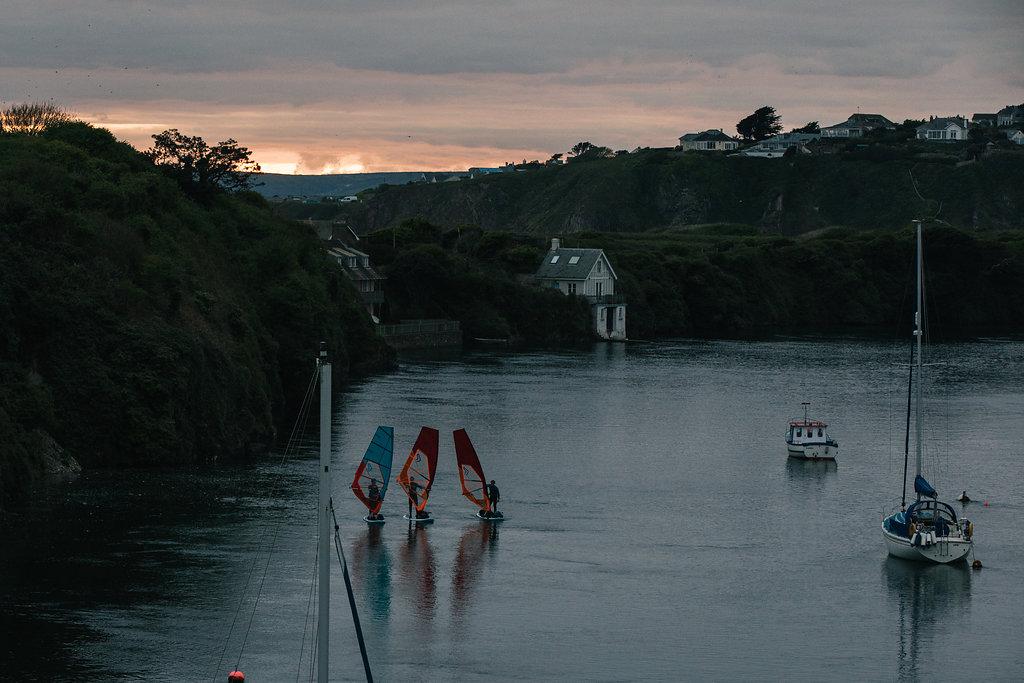 Sunset 3 males on windsurfs as sun goes down.