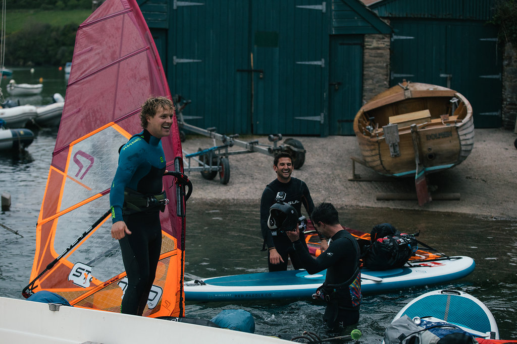 Male windsurfers, laugh and joke as they arrive at their destination.