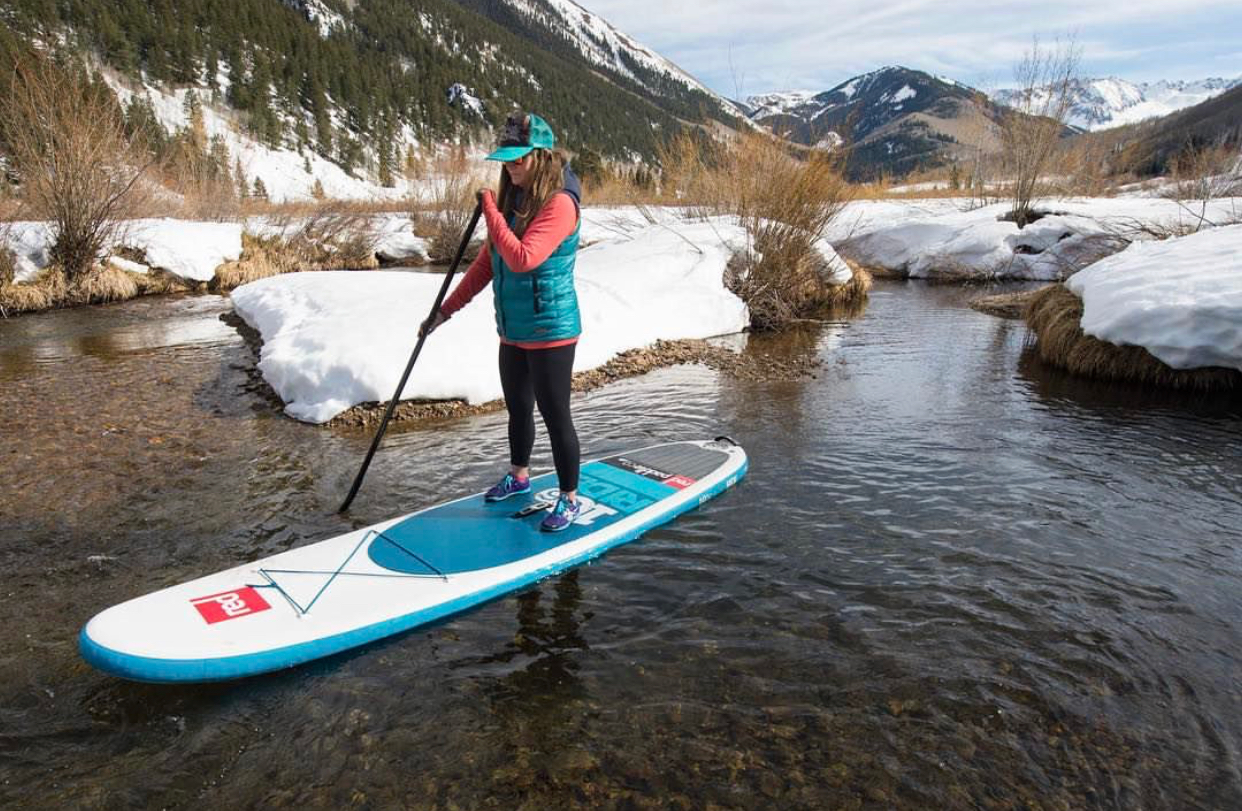 Stand up Paddler on river in snow