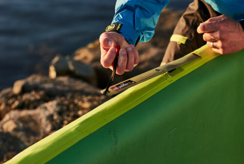 Close up inserting an RSS baton into a Red Paddle Co inflatable SUP