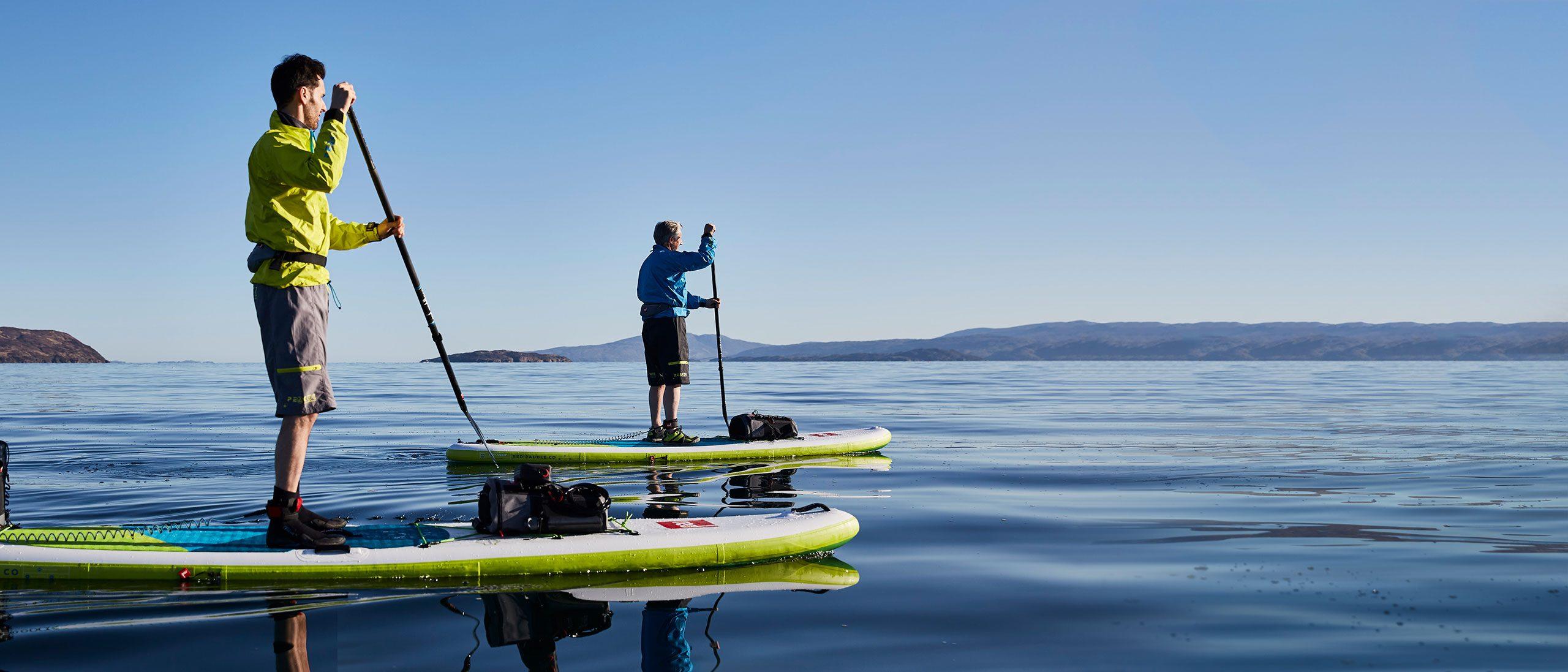 Zwei Freunde paddeln in flachen blauen Gewässern in Schottland