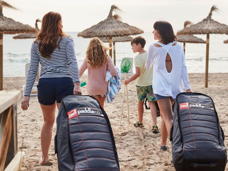 Two friends wheel their paddleboard bags onto beach
