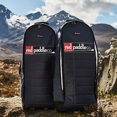 Two Red Paddle Co backpacks infront of snow-capped mountains