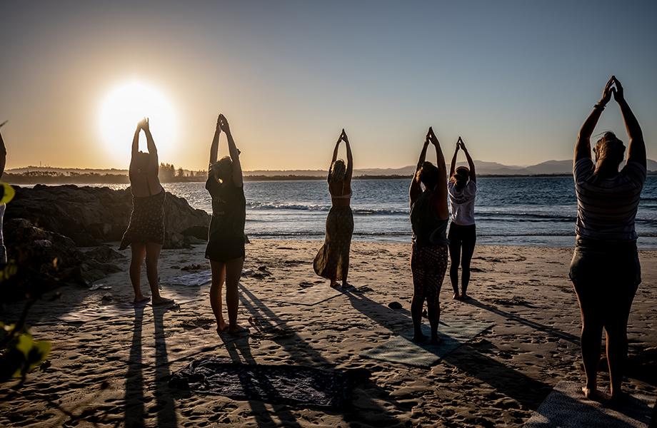 Group of women practicing yoga on the beach at sunrise