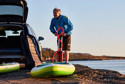 Man pumps up inflatable SUP