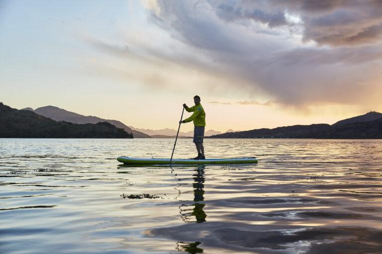 A loan paddle boarder paddling at sunset, Isle of Skye