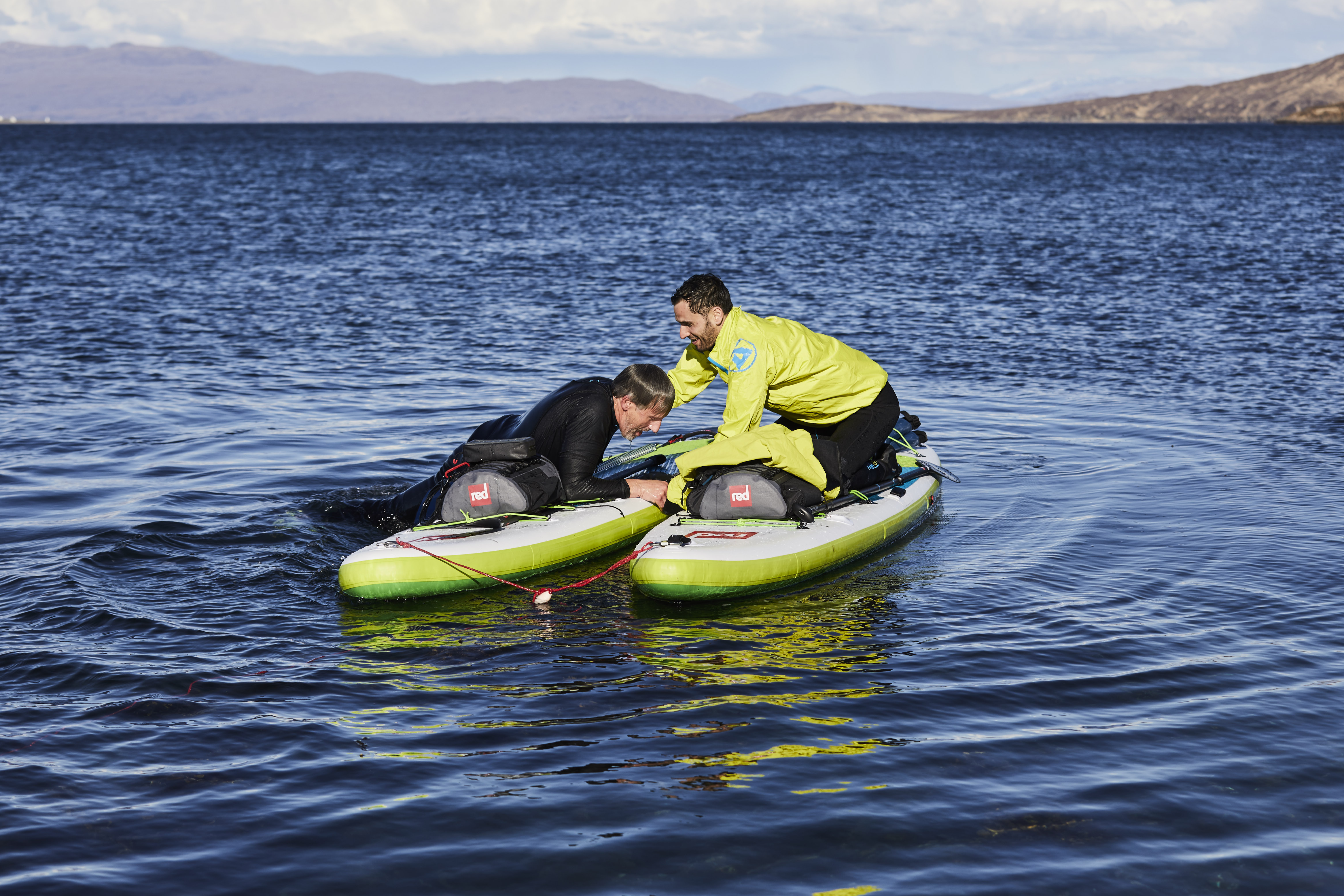 One male paddle boarder helps another back onto his inflatable paddle board after falling in