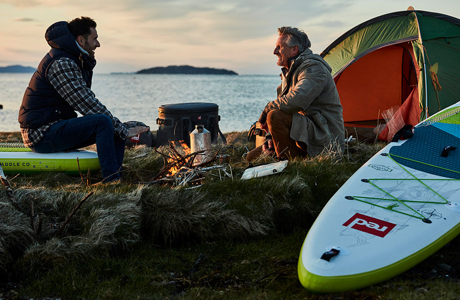 Friends sit next to camp fire with paddle board and tent in shot