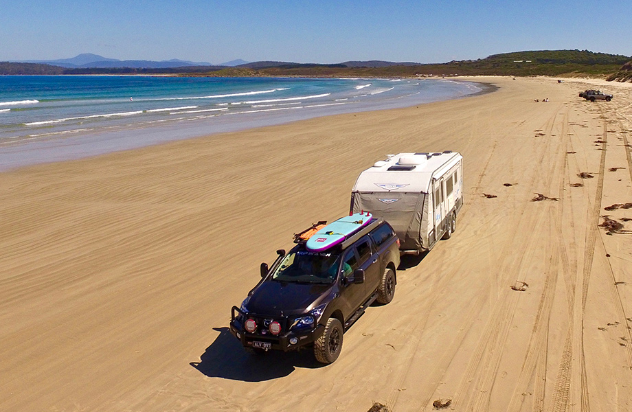 4x4 towing a caravan with a paddle bourdon roof on the beach