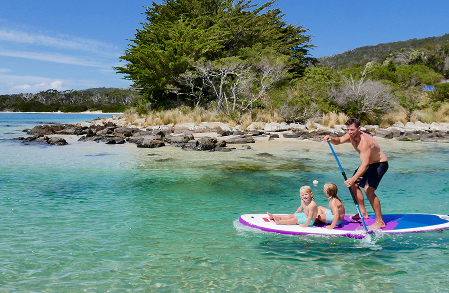 Man paddle boarding with two children on the front
