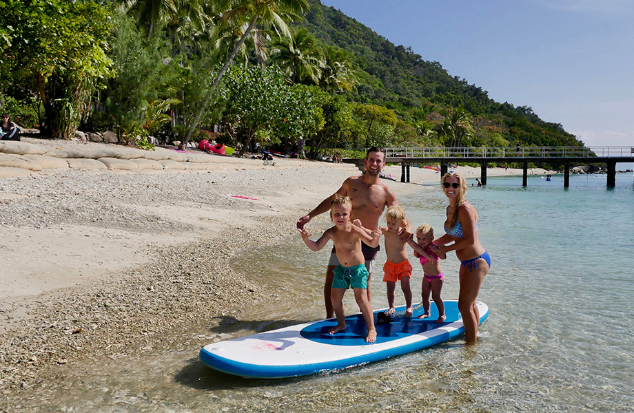 Family stood on paddle board in the shallow water