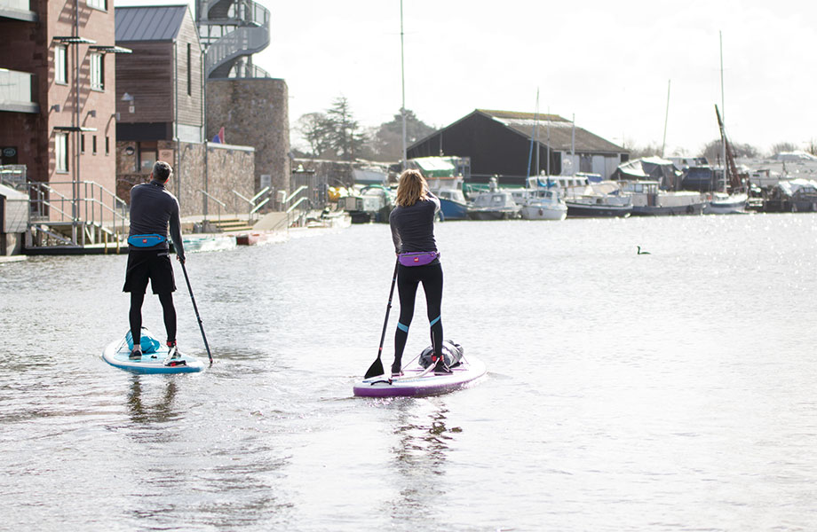 couple paddle in city quay on inflatable SUPs