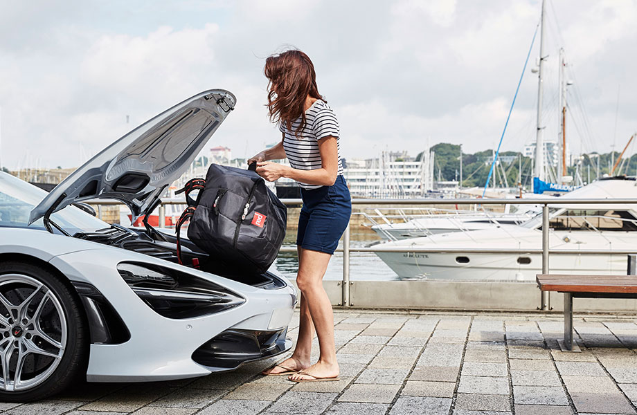 girl takes compact paddle board out of McLaren car