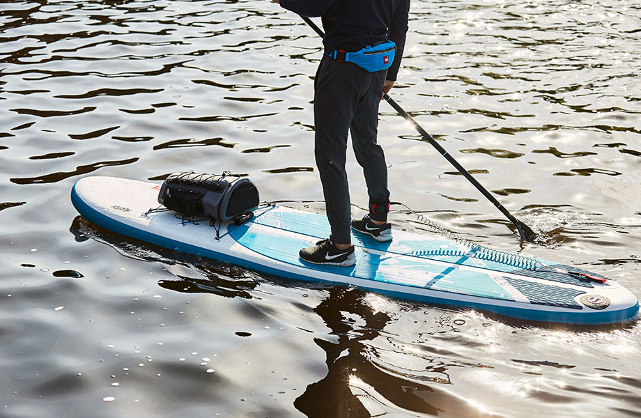 paddle boarder wears PFD and leash for safety on SUP