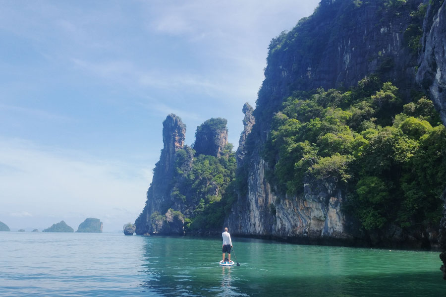 man paddles next to cliff edge in Thailand