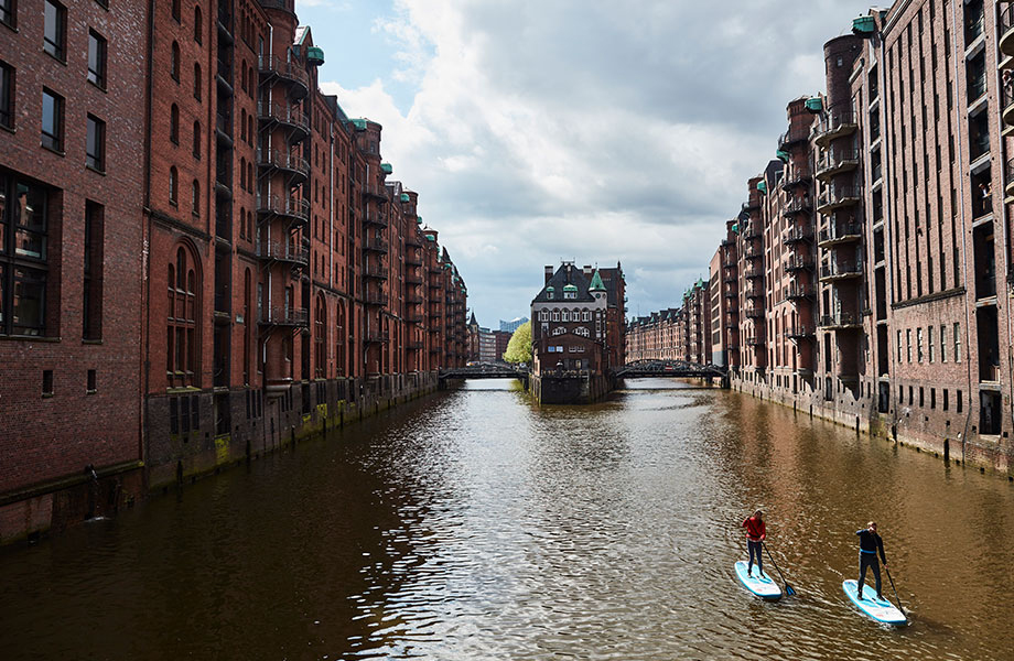 two paddle boarders in Hamburg on canal.