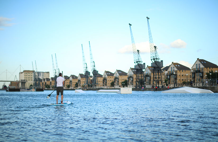 Man stands looking at city skyline on paddle board