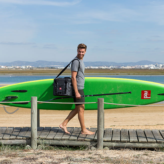 Carrying cool bag and paddle board to beach