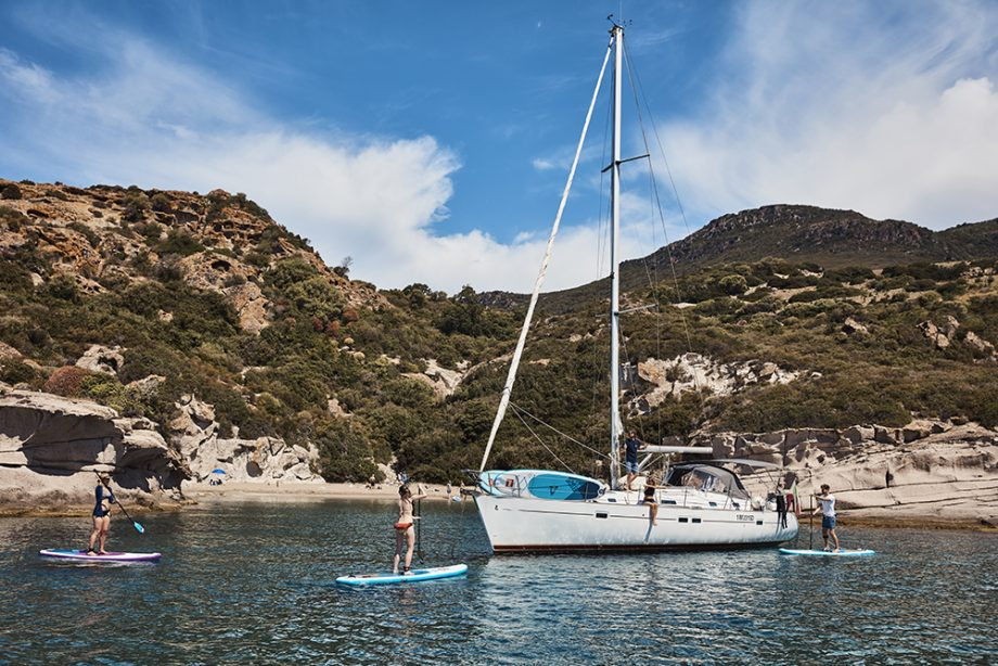 Paddle boarders in crystal clear water alongside a yacht