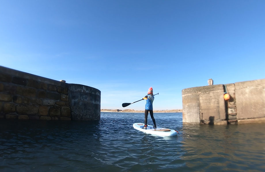 Child paddles on SUP with bobble hat in winter