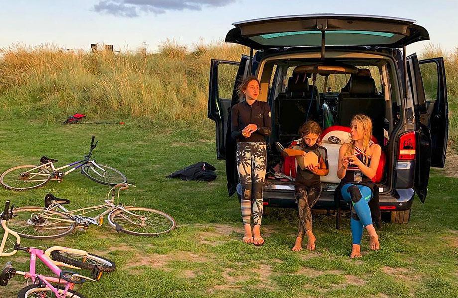 Kids sit in back of van and eat snacks in their wetsuits