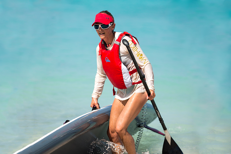 woman walks out of turquoise sea with SUP board