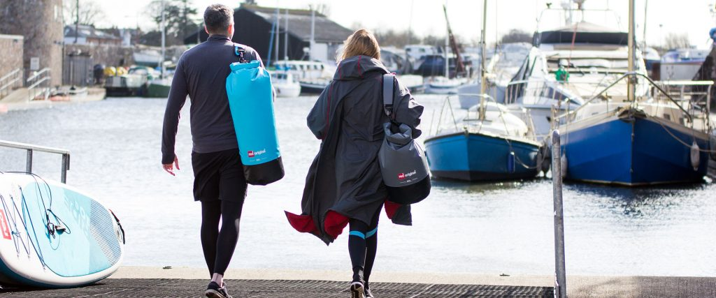 couple walk towards the water carrying Red Original dry bags