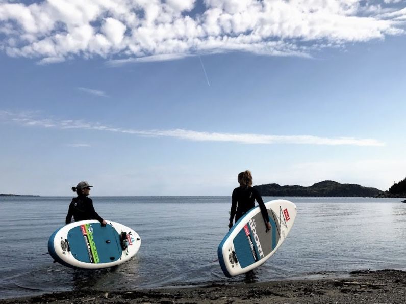 Man & Woman Holding Paddle Boards On The Shore, Canada