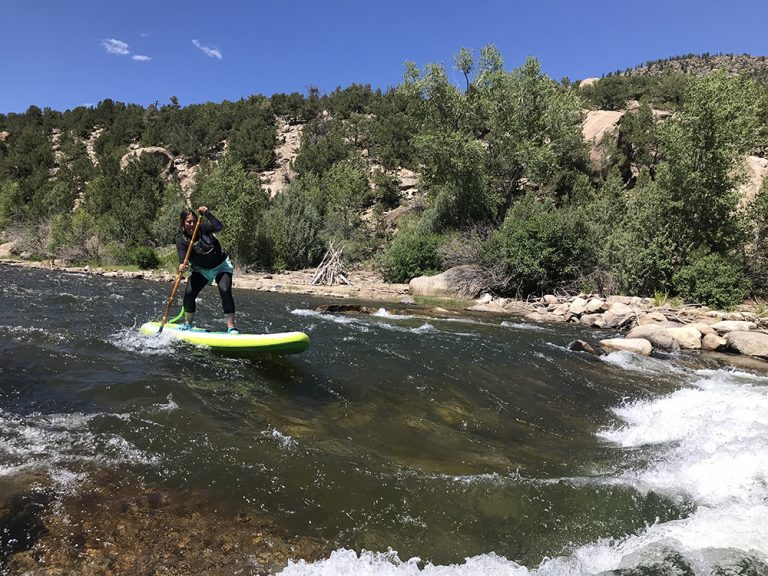 Woman paddles white water in Aspen Colorado